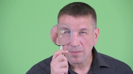 osobní strážce : Face of macho mature businessman as detective inspecting with magnifying glass Dostupné videozáznamy