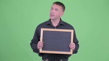 osobní strážce : Macho mature businessman talking while holding blackboard
