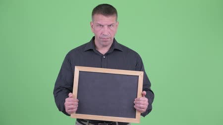 garde du corps : Angry macho mature businessman holding blackboard