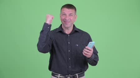 osobní strážce : Happy macho mature businessman using phone and getting good news