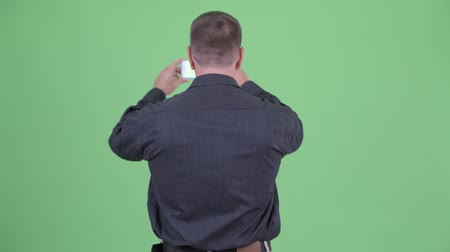 osobní strážce : Rear view of macho mature businessman taking picture with phone