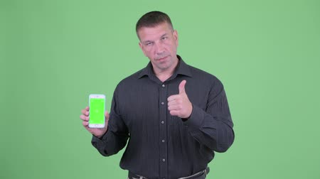 osobní strážce : Macho mature businessman showing phone and giving thumbs up Dostupné videozáznamy