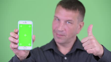 телохранитель : Face of macho mature businessman showing phone and giving thumbs up