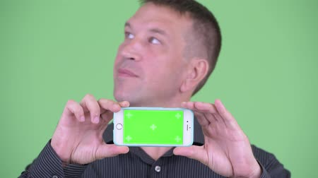 osobní strážce : Face of macho mature businessman thinking while showing phone Dostupné videozáznamy
