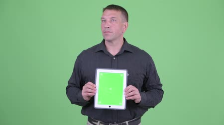 gengszter : Macho mature businessman thinking while showing digital tablet Stock mozgókép