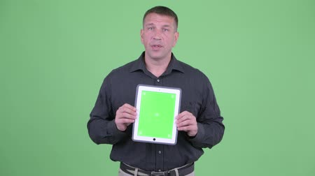 osobní strážce : Macho mature businessman talking while showing digital tablet