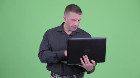 гангстер : Macho mature businessman thinking while using laptop Стоковые видеозаписи
