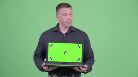 osobní strážce : Macho mature businessman thinking while showing laptop