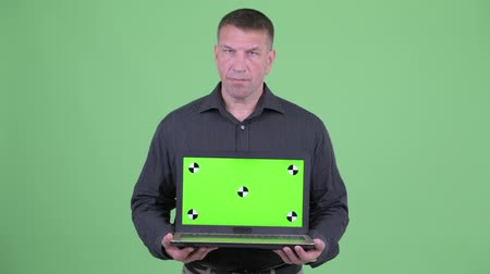 mafia : Angry macho mature businessman showing laptop