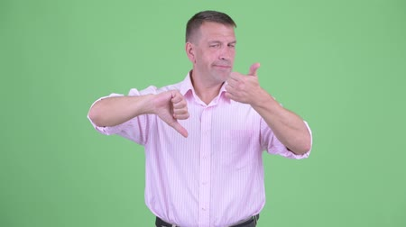 fikirler : Confused mature macho businessman choosing between thumbs up and thumbs down