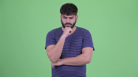 think big : Stressed young overweight bearded Indian man thinking