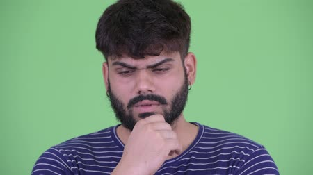 think big : Face of stressed young overweight bearded Indian man thinking Stock Footage