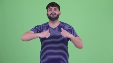 vélemény : Confused young overweight bearded Indian man choosing between thumbs up and thumbs down