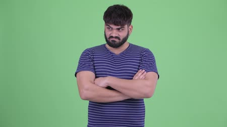 furioso : Angry young overweight bearded Indian man with arms crossed