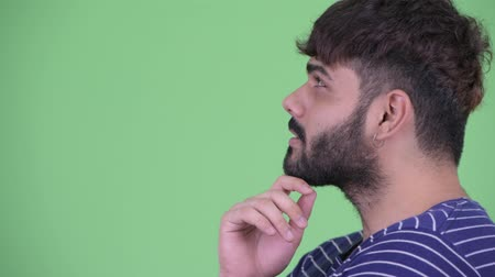 think big : Closeup profile view of happy young overweight bearded Indian man thinking