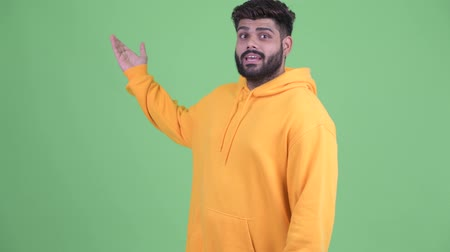 capuchon : Happy young overweight bearded Indian man vlogging and talking to camera Stockvideo