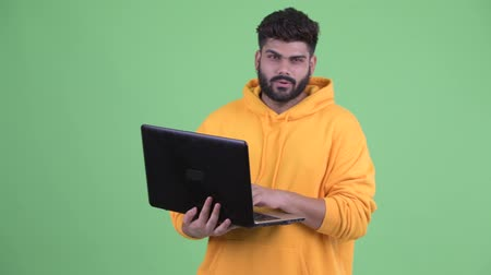 vlogging : Happy young overweight bearded Indian man talking while using laptop