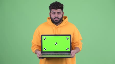 slecht nieuws : Stressed young overweight bearded Indian man showing laptop