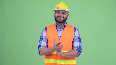 ovation : Happy young overweight bearded Indian man construction worker clapping hands