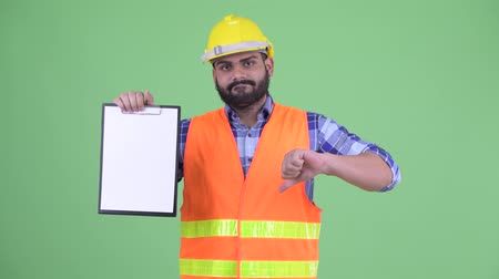 check list : Stressed overweight bearded Indian man construction worker showing clipboard and giving thumbs down