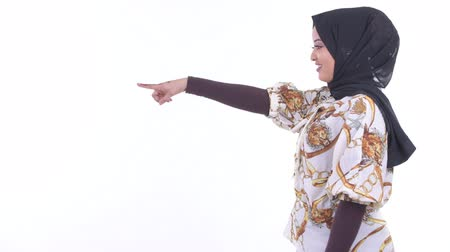 direkt : Profile view of happy young African Muslim woman pointing finger