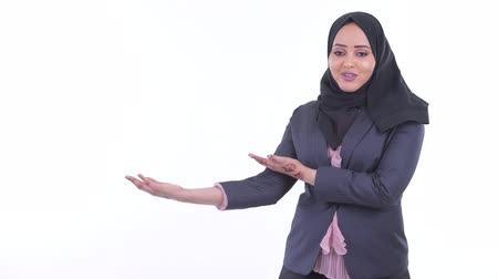 átnyújtás : Happy young African Muslim businesswoman talking while showing something