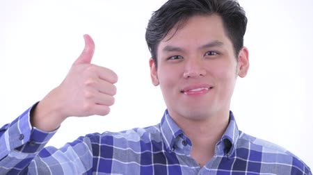 клетчатый : Face of happy young Asian hipster man giving thumbs up