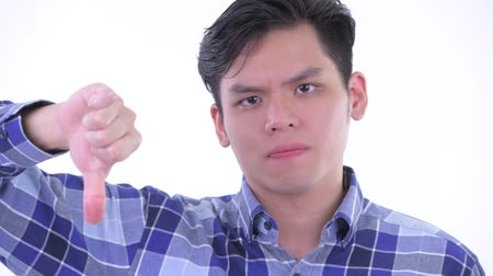 singaporean : Face of stressed young Asian hipster man giving thumbs down Stock Footage