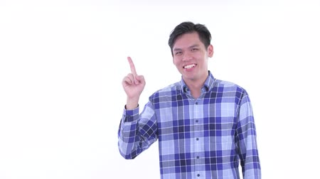 singaporean : Happy young Asian hipster man talking while pointing up Stock Footage