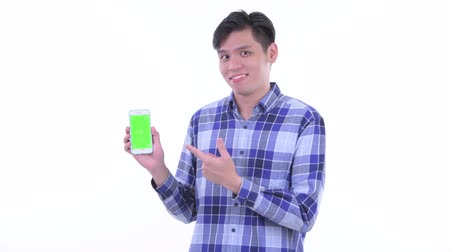 singaporean : Happy young Asian hipster man showing phone and giving thumbs up Stock Footage