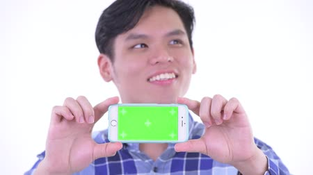 singaporean : Face of happy young Asian hipster man thinking while showing phone