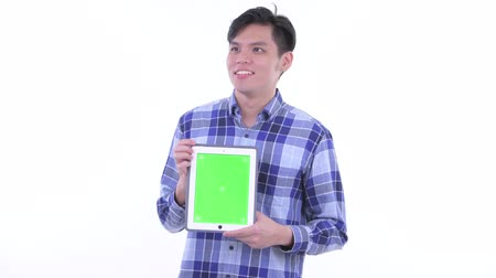 singaporean : Happy young Asian hipster man thinking while showing digital tablet