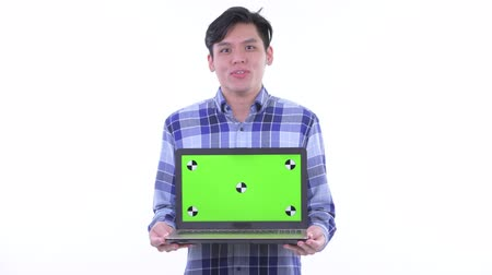 singaporean : Happy young Asian hipster man showing laptop and looking surprised