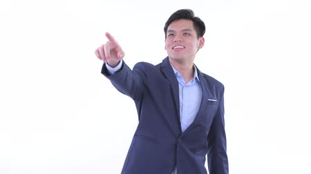 direkt : Happy young Asian businessman pointing finger and directing Stok Video