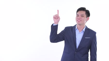 idéia genial : Happy young Asian businessman thinking and pointing up Vídeos