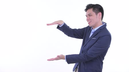 singaporean : Happy young Asian businessman snapping fingers and showing something
