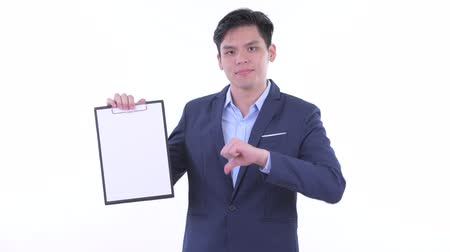 singaporean : Stressed young Asian businessman showing clipboard and giving thumbs down
