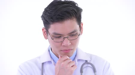 singaporean : Face of stressed young Asian man doctor thinking and looking down Stock Footage