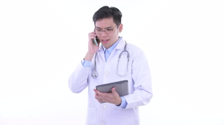 singaporean : Happy young Asian man doctor using phone and digital tablet