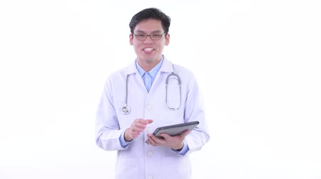 singaporean : Happy young Asian man doctor thinking while using digital tablet Stock Footage
