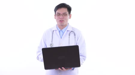 singaporean : Happy young Asian man doctor talking while using laptop