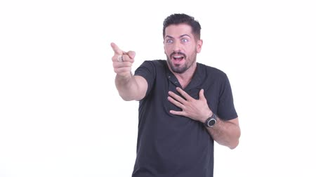positief denken : Happy young handsome bearded man pointing finger and looking surprised Stockvideo