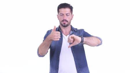 fikirler : Confused young bearded hipster man choosing between thumbs up and thumbs down Stok Video