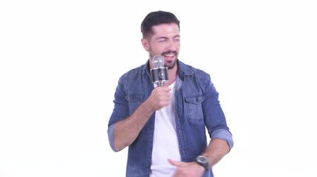 evsahibi : Happy young bearded hipster man as host using microphone Stok Video