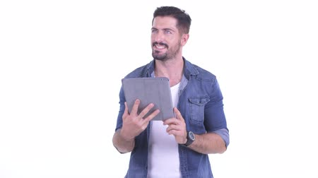 denim : Happy young bearded hipster man thinking while using digital tablet Stock Footage