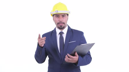 check list : Happy bearded Persian businessman as engineer talking while holding clipboard Stockvideo