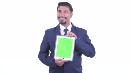 ближневосточный : Happy bearded Persian businessman thinking while showing digital tablet Стоковые видеозаписи