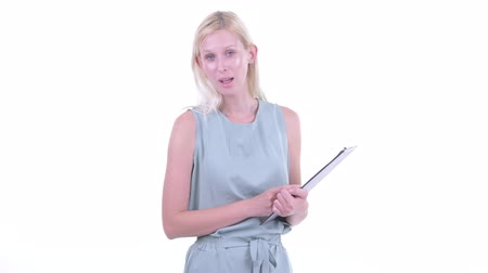 kolsuz : Happy young beautiful blonde woman talking while holding clipboard Stok Video