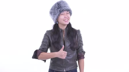 Happy beautiful Asian woman giving thumbs up