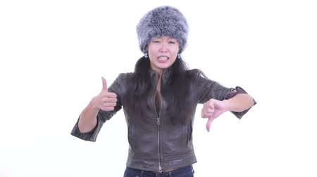 Confused Asian woman choosing between thumbs up and thumbs down Wideo